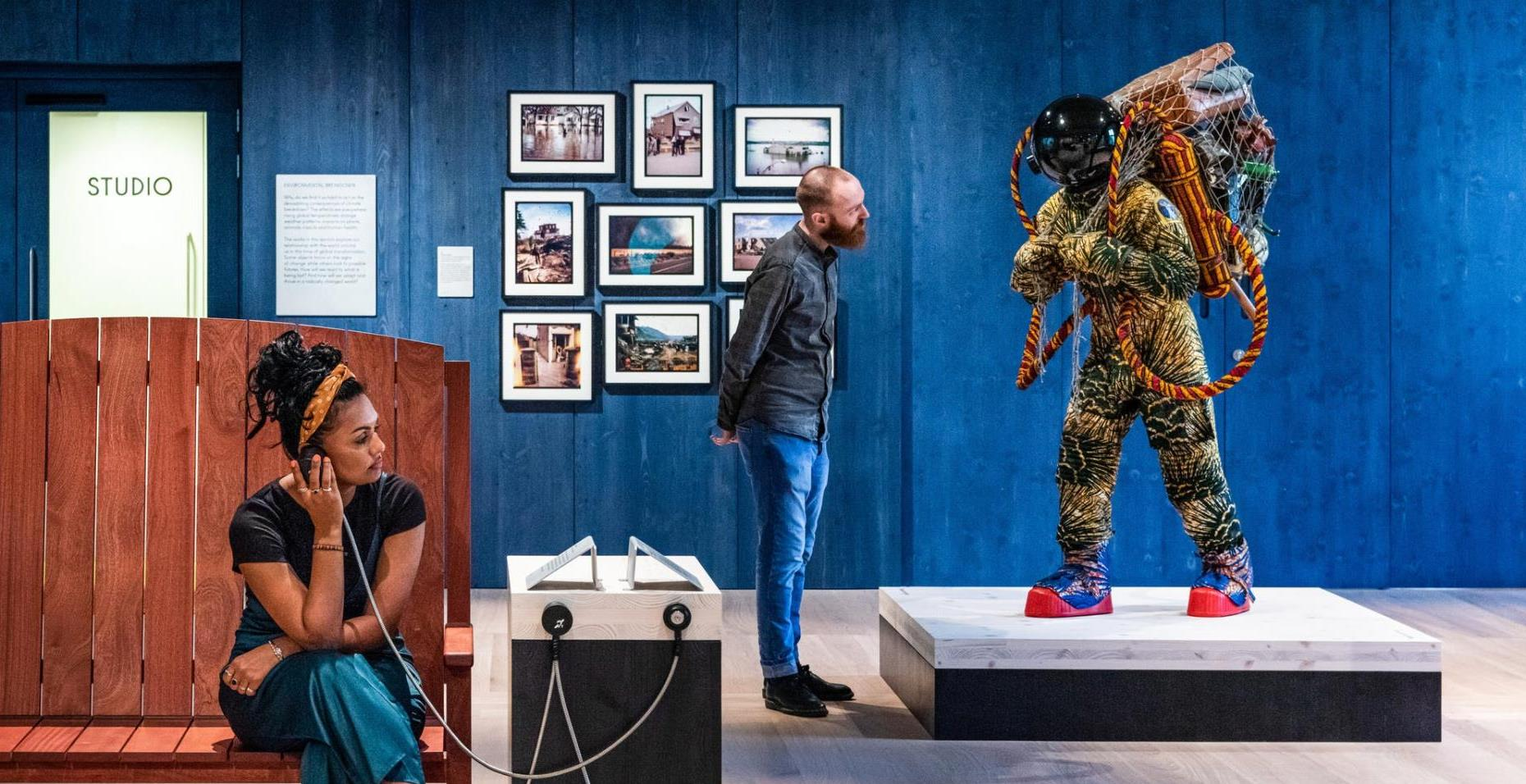Photograph of Being Human gallery, with a blue stained wood wall in the background, in front of which a young man looks at a life-size artwork of a figure resembling an astronaut. In the foreground a young woman sits on a wooden bench holding an audio speaker to her ear