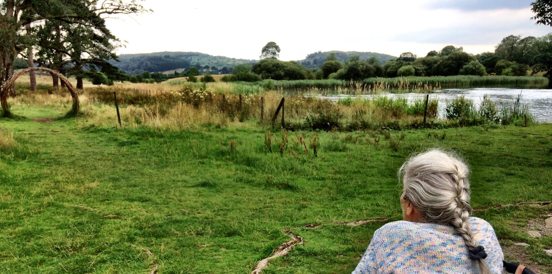 Photo shows a lady in a wheelchair looking out on to the meadow section of the park with the lake to her right. We were still on a hard packed path at this point.