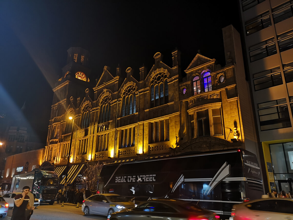 The exterior of Albert Hall Manchester lit up at night.