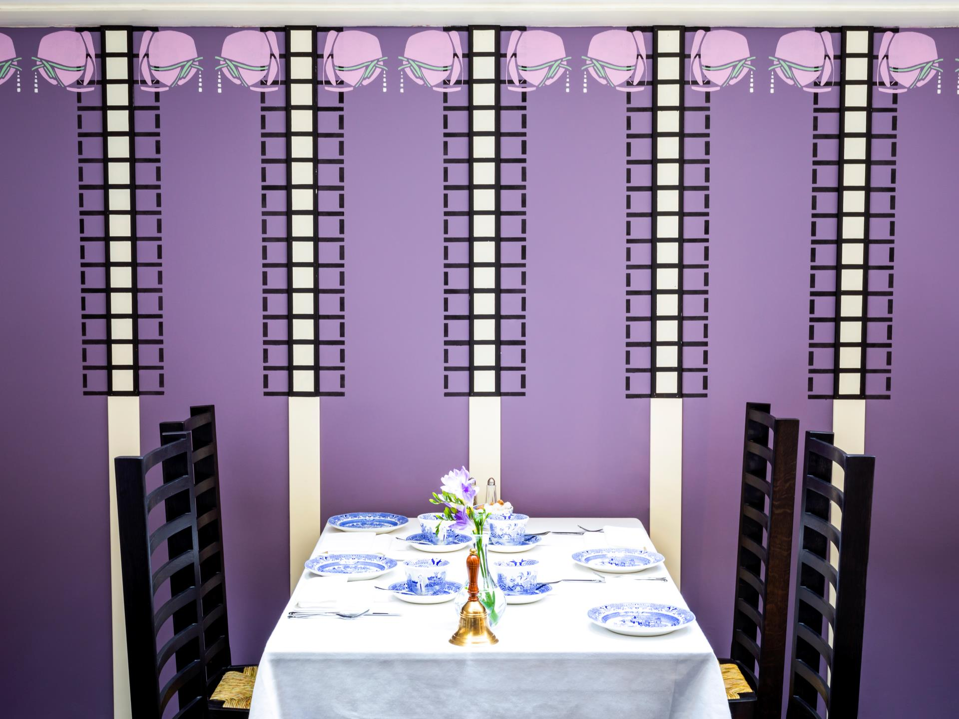 Table setting in the Gallery of the Tea Rooms showing stencilling detail on the wall panels and ladder back chairs. The table is set with Blue Willow pattern Burleigh crockery.